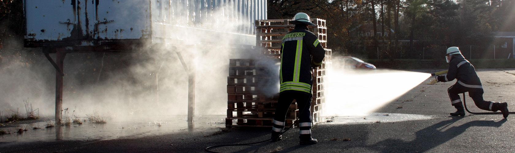 Brandschutzwache beim Training - brennendes Holz löschen
